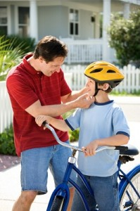 Dad helping son with bike helmet.